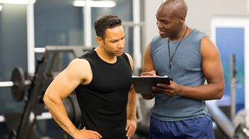 34100686 - african personal trainer helping man to fill the membership form of health club